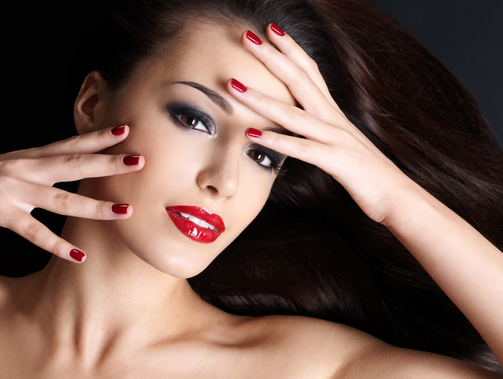 Smiling woman with red painted nails on her face