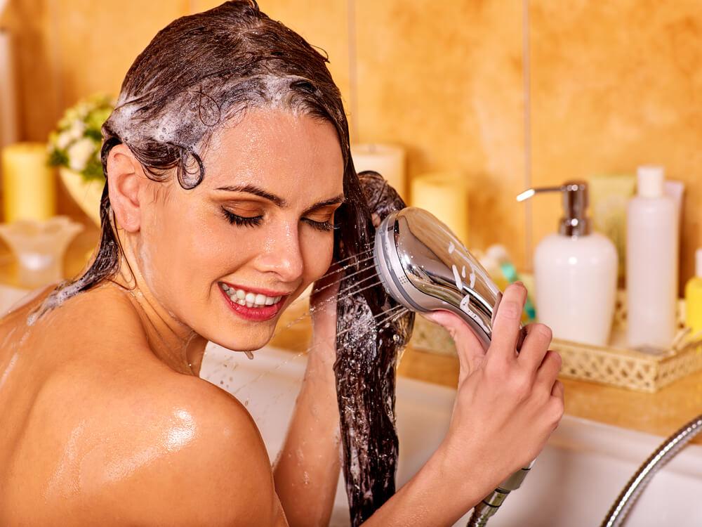 Woman washing her hair in bathtub