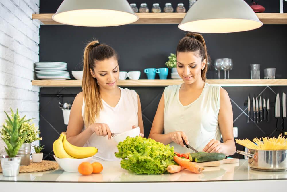 two women preparing salad in the kitchen