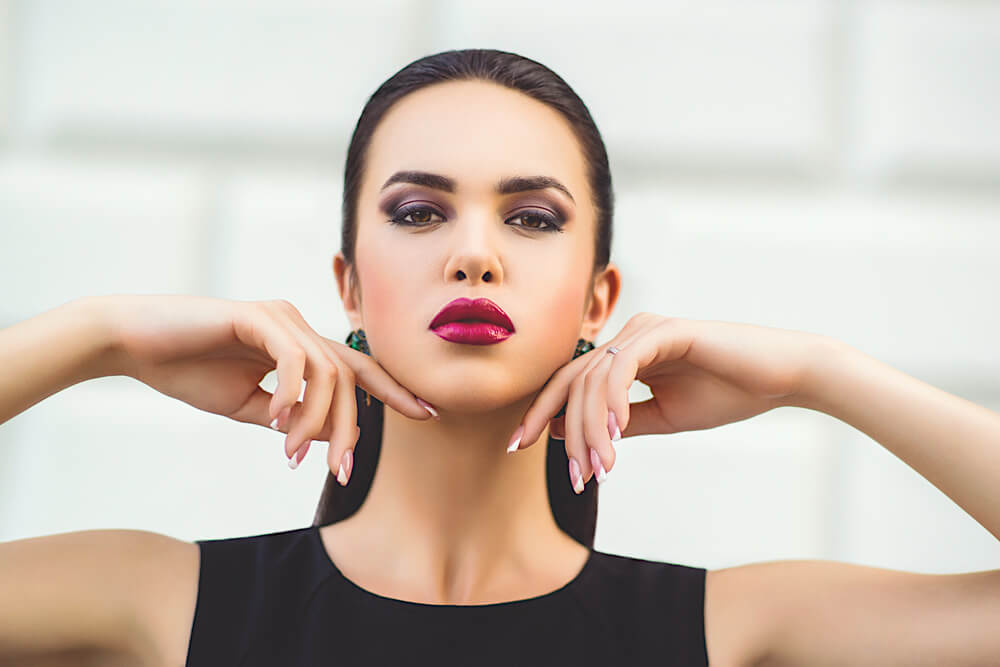 brunette woman touching her face