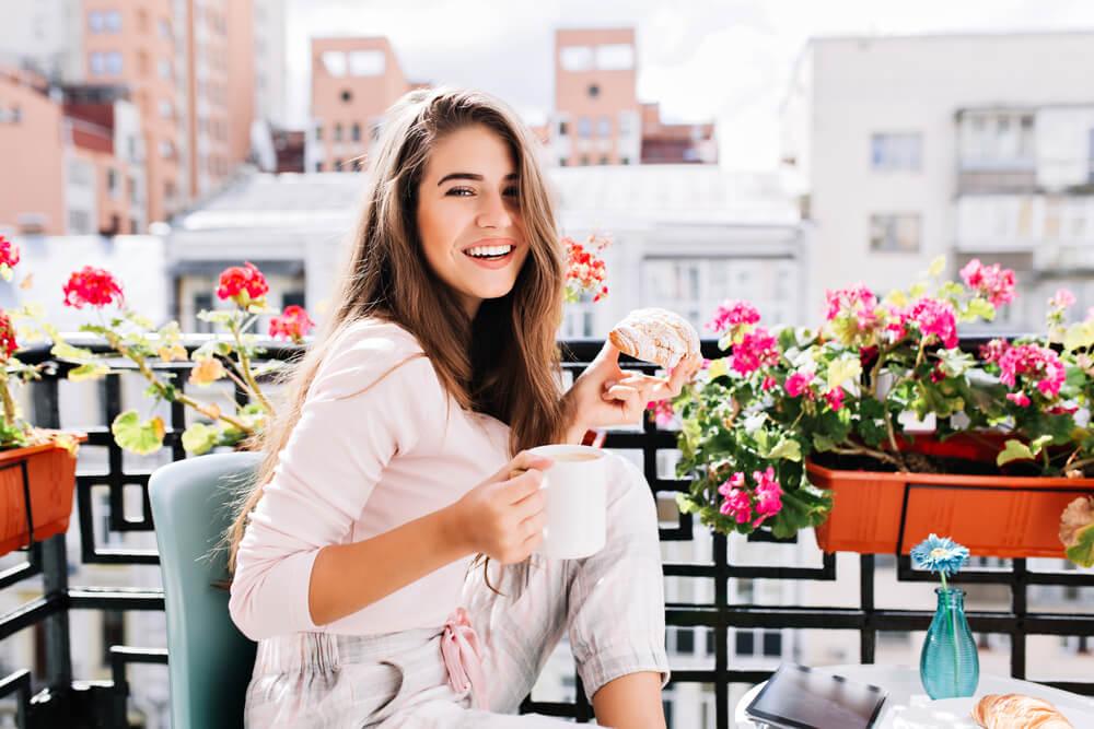 woman having breakfast in an apartment balcony