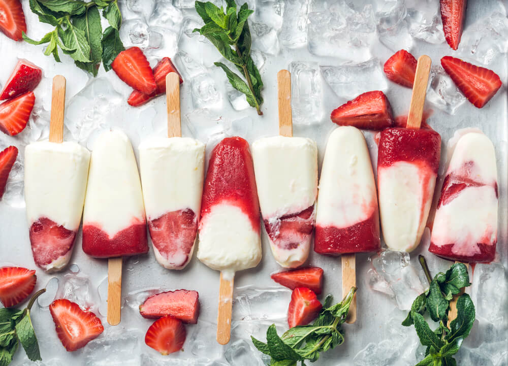 Strawberry yogurt popsicles on table
