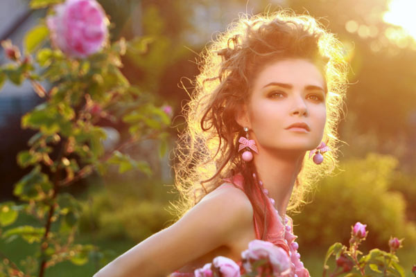 Woman with curly hairstyle outdoors in a garden