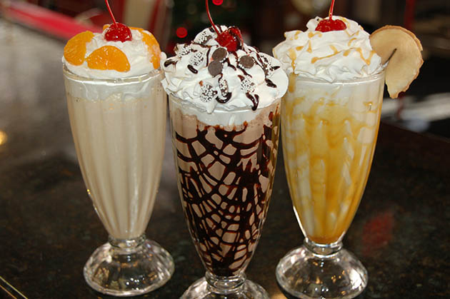 Multiple milkshakes topped with whipped cream and sauces