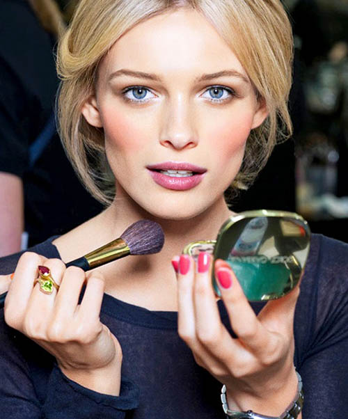 Attractive woman applying makeup using compact mirror