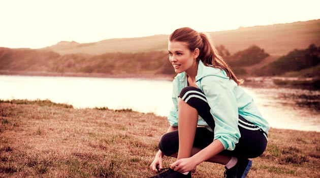 Smiling woman tying up shoelaces outdoors