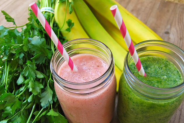 Pink and green smoothies surrounded by bananas and leafy greens