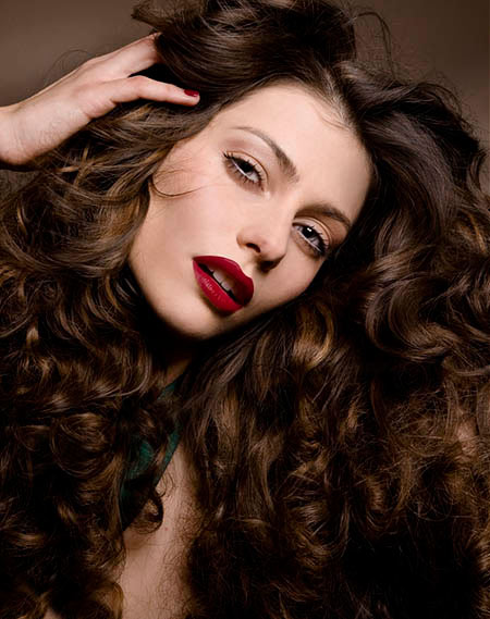 Woman with wavy long brown hair and red lipstick