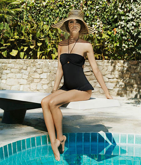 Woman with hat sitting by the pool