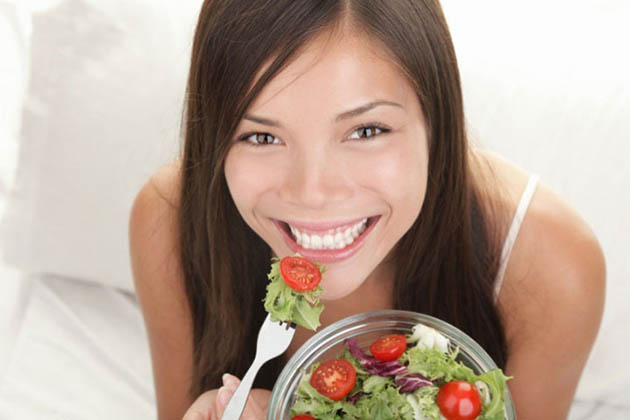 Woman eating salad from bowl