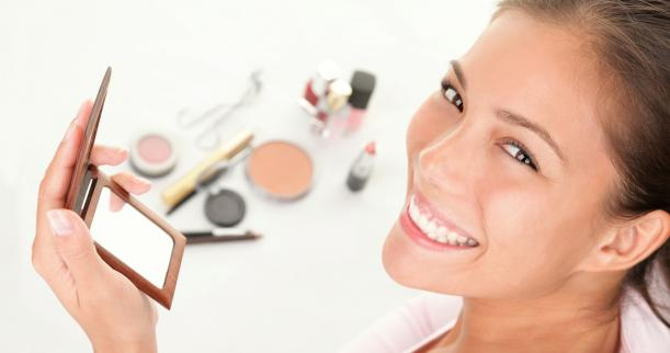 Woman with assorted makeup products on white background
