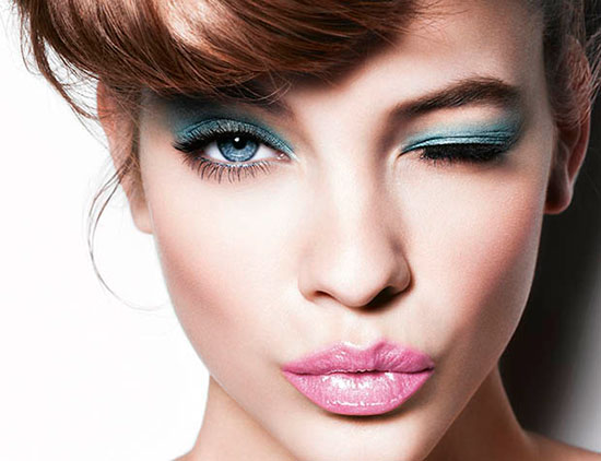 Woman with turquoise eyeshadow and pink lipstick