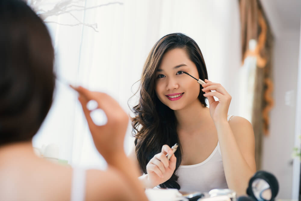 woman applying mascara at dressing table
