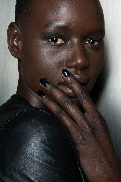 Woman with black nails touching skin