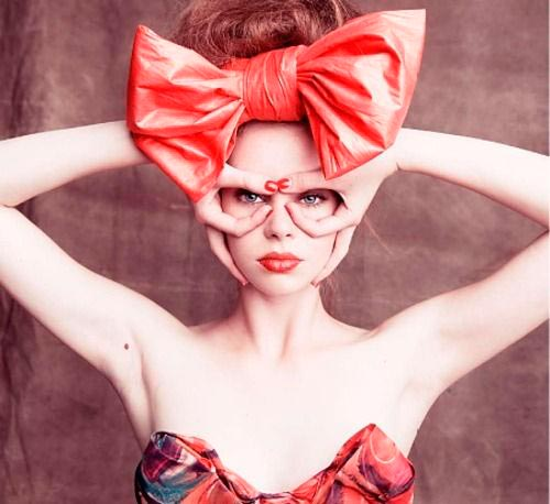 Woman with extra large red bow in hair