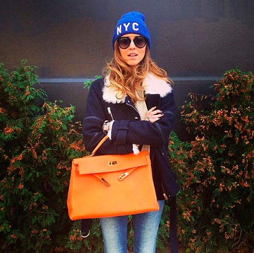 Fashionable woman with bright handbag and blue beanie