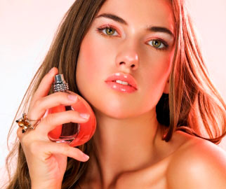 Woman holding perfume next to face