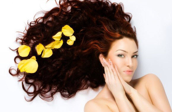Woman with thick dark wavy hair and yellow petals
