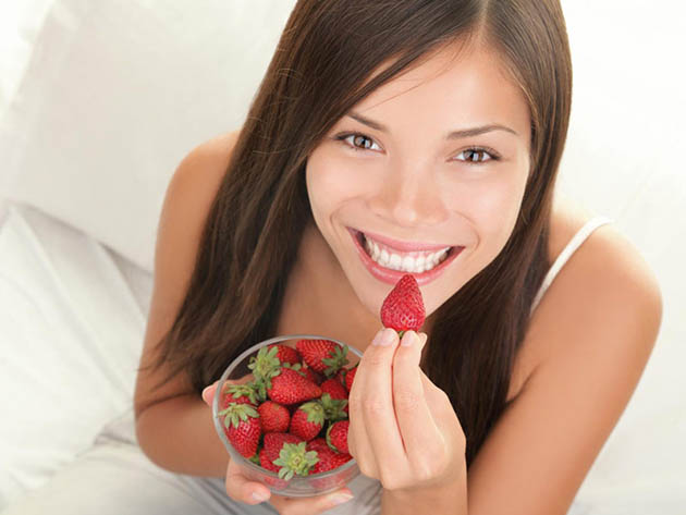 Woman eating strawberry from bowl