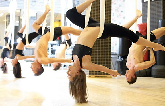 Group performing aerial yoga in studio