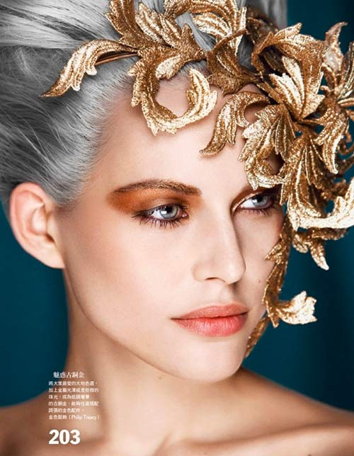Model with metallic bronze eyeshadow and gold hair accessory