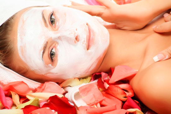 Woman with white facial mask surrounded by flower petals