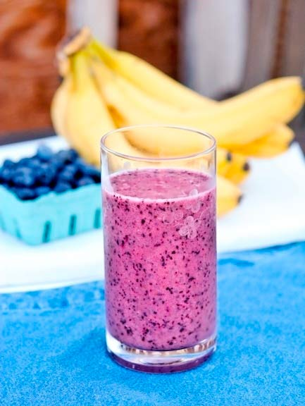 Pink smoothie with banana and blueberries in the background