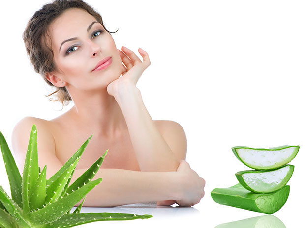 Woman with clear skin surrounded by aloe vera