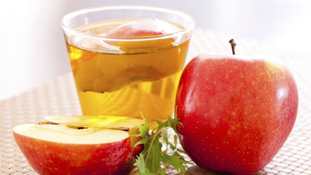 Apple cider vinegar surrounded by whole and halved apples