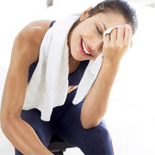 Woman wiping away sweat with a towel