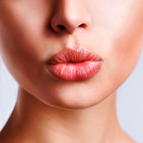 Woman's pout in red lip balm