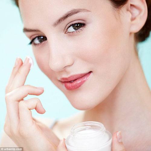 Woman applying moisturizer to eyes