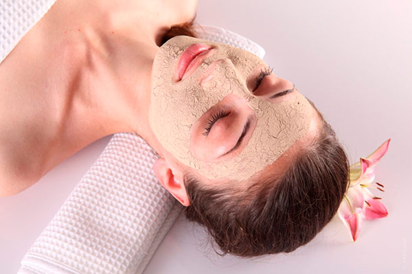 Woman with face mask relaxing on towel