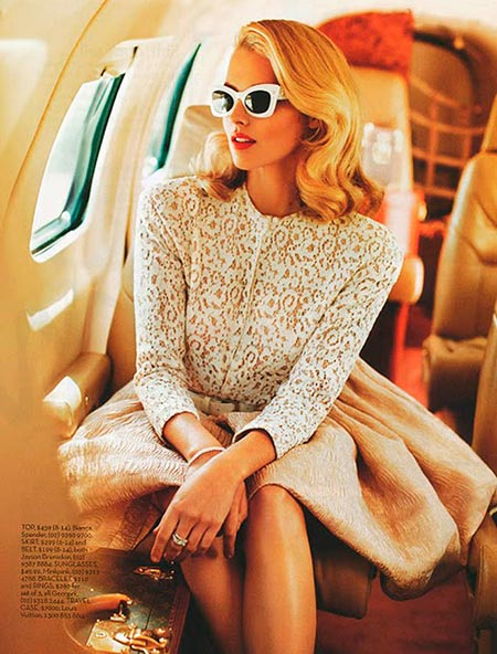Woman with fancy white-framed sunglasses on a plane