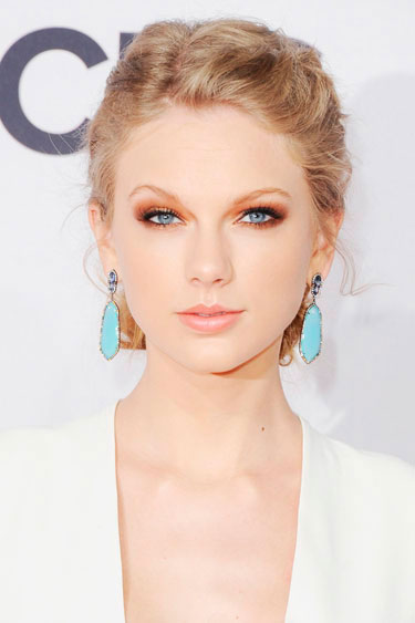 Taylor Swift with bright blue earrings and orange-hued makeup