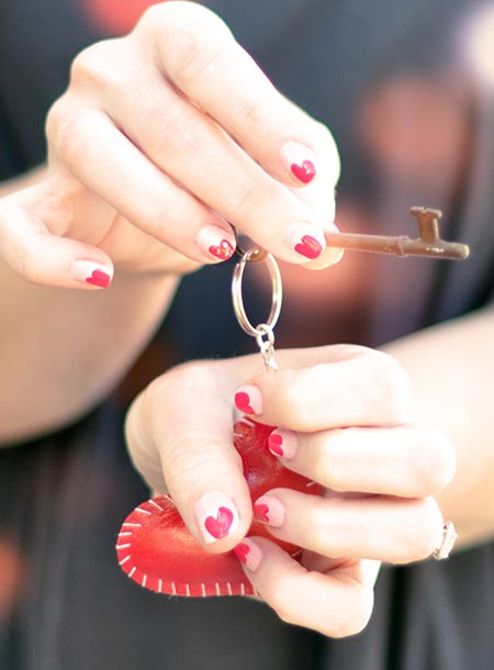 Woman's hands with red keychain and heart-shaped manicure