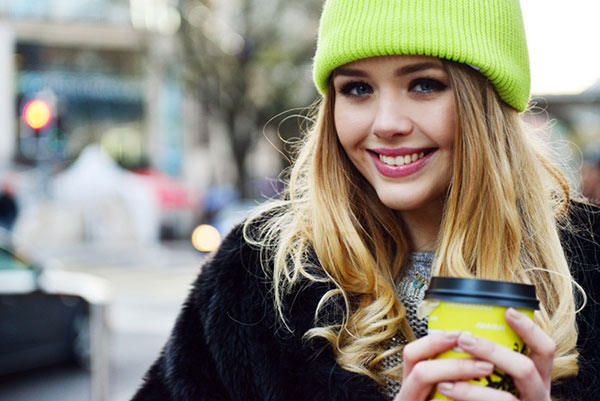 Woman in beanie holding a cup of coffee