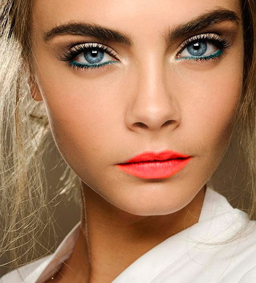 Cara Delevingne with dark eye makeup and scarlet lipstick