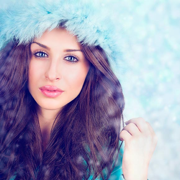Model with long brunette hair and blue feather crown
