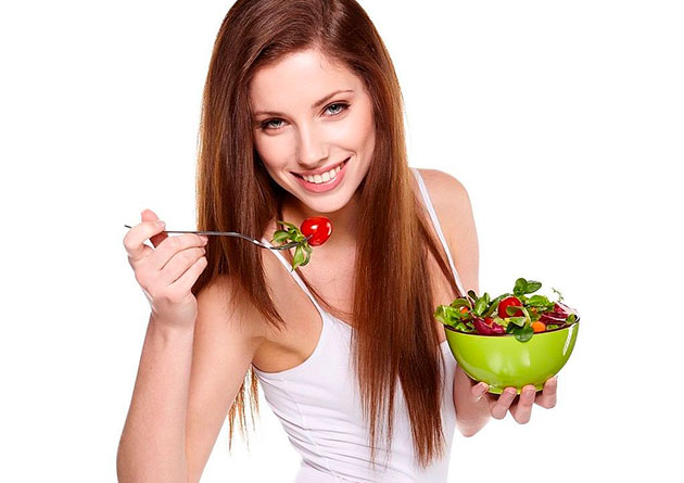 Woman eating salad from green bowl