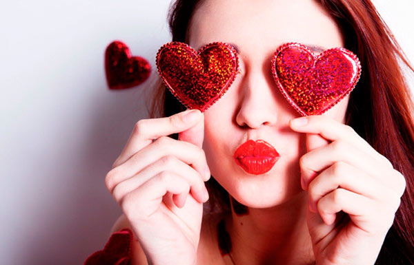 Woman holding heart-shaped accessories on her eyes
