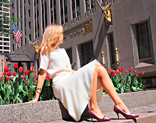 Fashionable woman outdoors in heels and a white dress