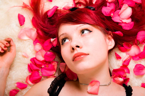 Woman with red hair and pink petals