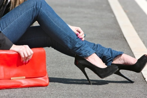 Woman's legs in denim jeans and high heels with a red purse