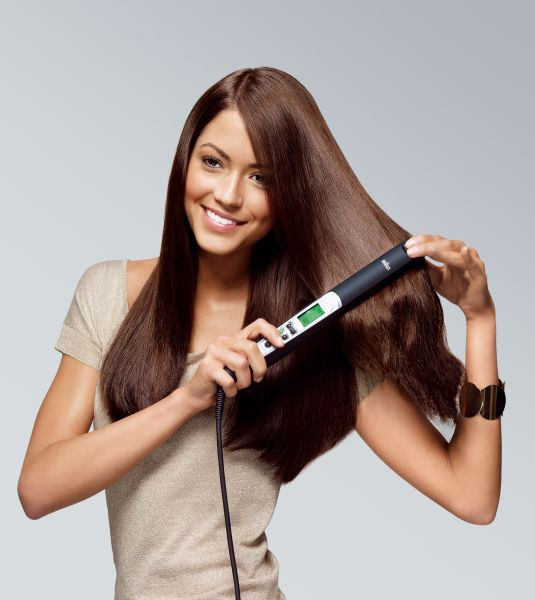 Woman using a hair straightener