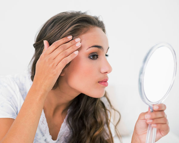 Woman examining her skin in mirror