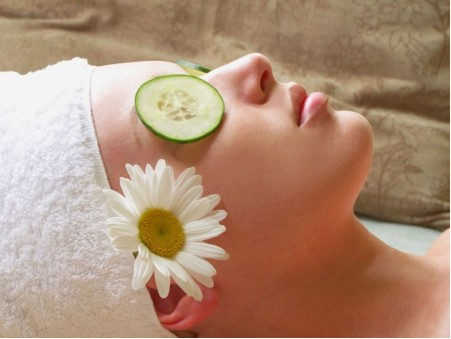 Woman with cucumber slice on eye and flower tucked by her ear