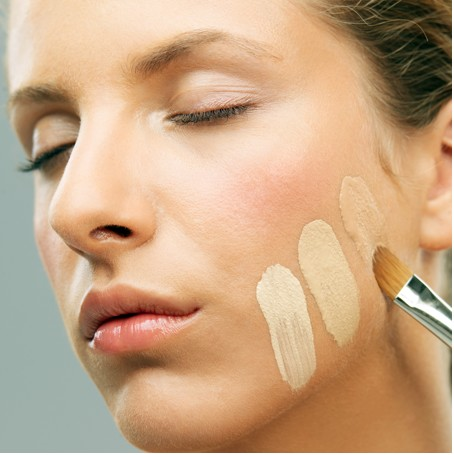 Woman applying foundation to skin