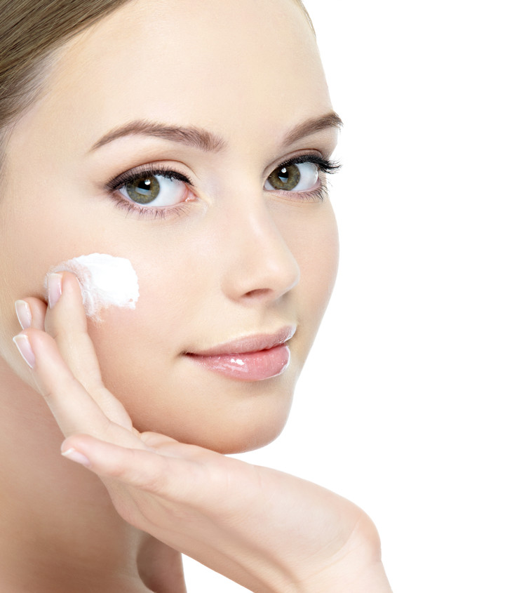 Woman applying skincare product to cheek