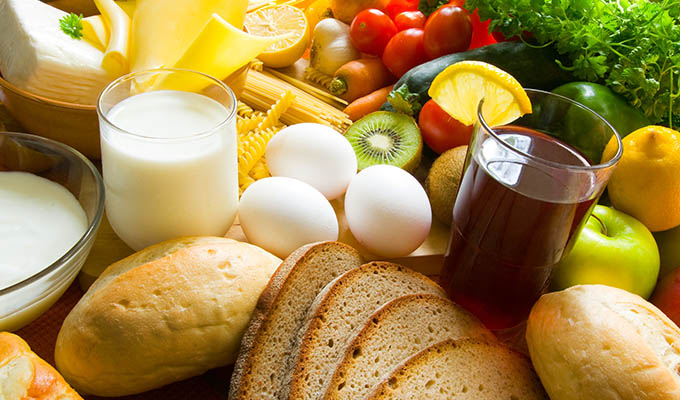 Assorted food on display, including milk, white eggs, bread, fruits and vegetables